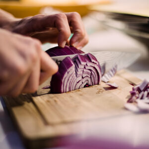 Cutting a red onion with a knife on a cutting board